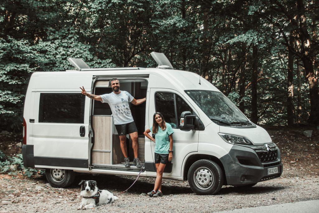 Pareja de viajeros con su perro y su furgoneta a punto de comenzar la excursión del Turó de l'Home