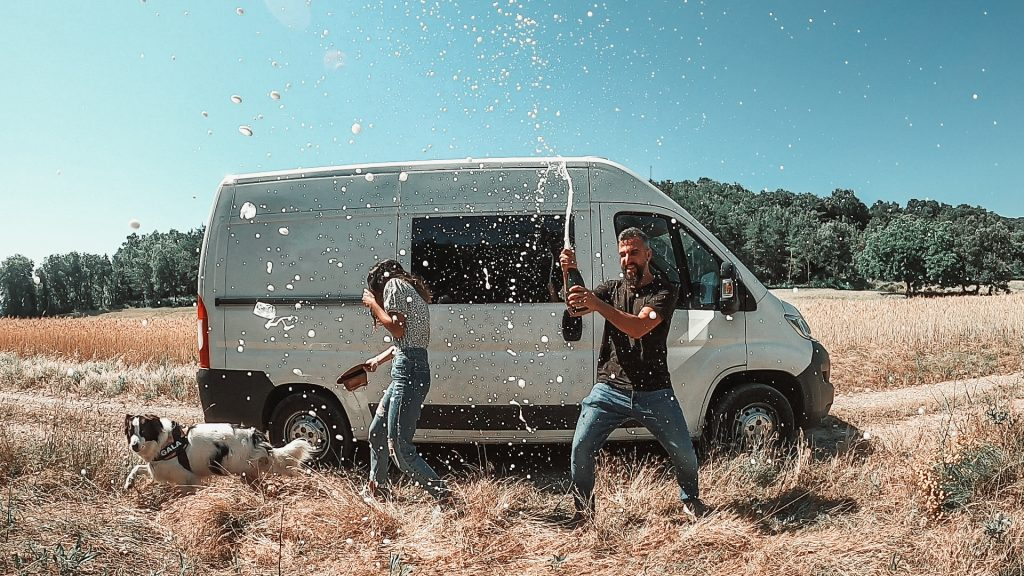 Galaventura celebrando con champagne delante de la furgoneta camper